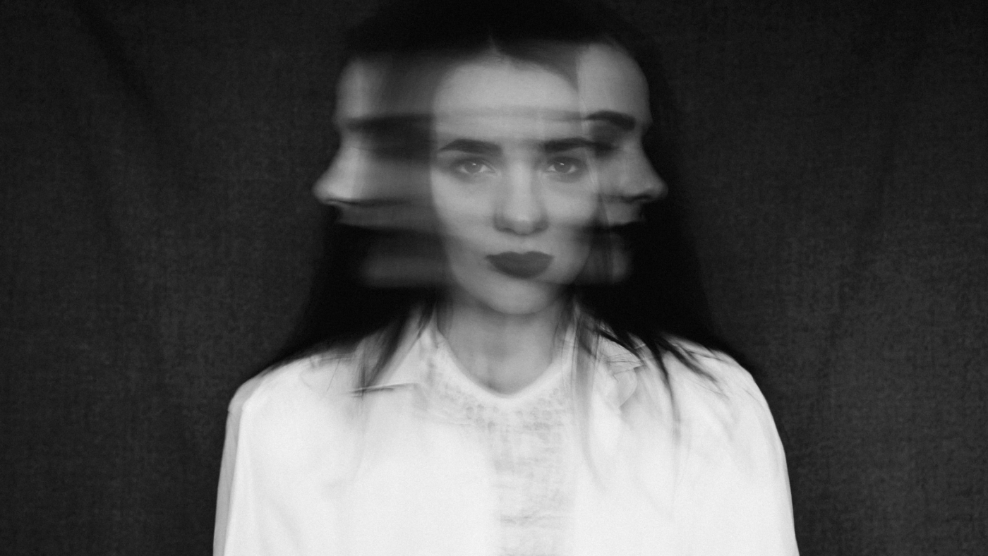 crazy portrait of a girl with mental disorders and split personality. Black and white in vintage style with added grain and motion blur