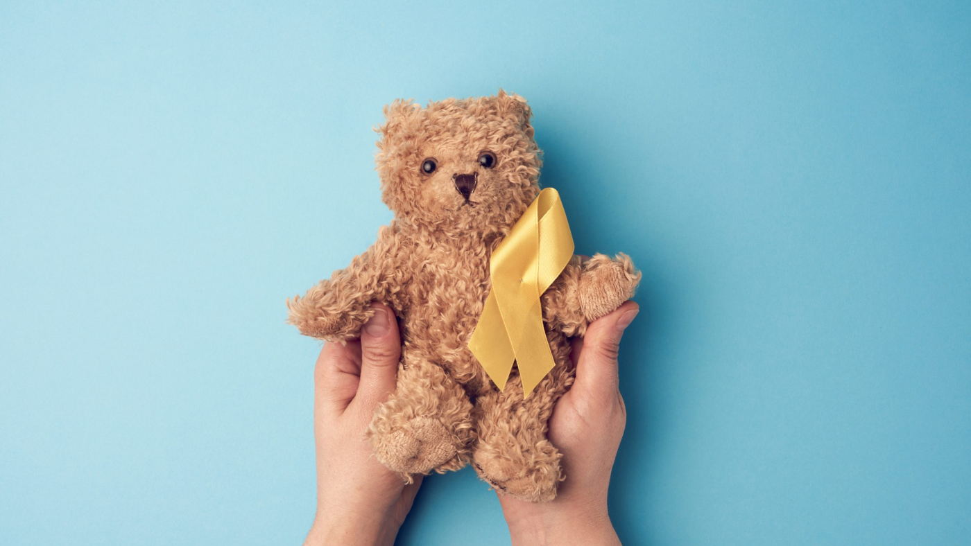 female hands hold a small teddy bear with a yellow ribbon folded in a loop on a blue background. concept of the fight against childhood cancer. problem of suicides