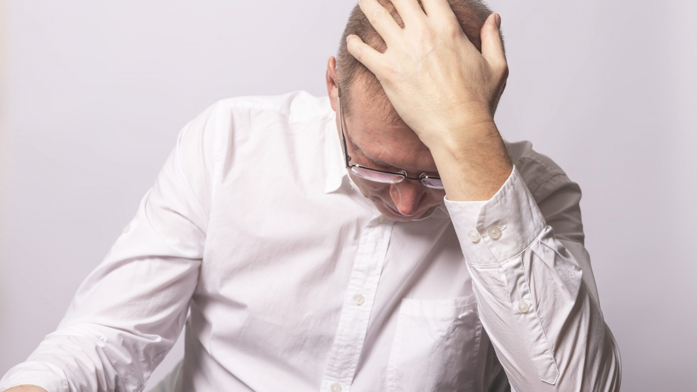 Depressed businessman in anxiety with hand on head. Tired man in panic. Worrying human.