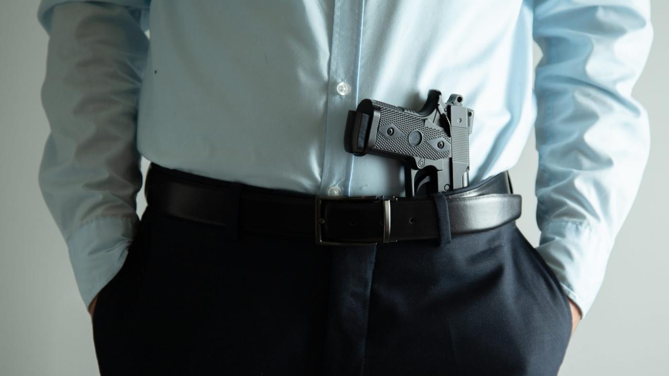 man hand holding gun on grey background