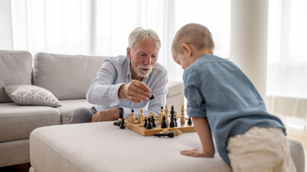 The adorable little boy playing chess with his grandfather