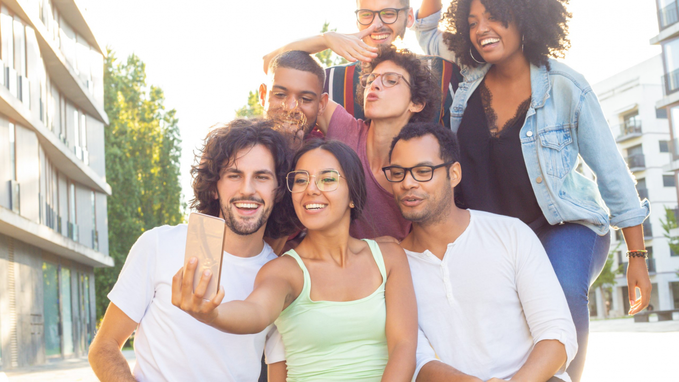 Joyous mix raced people taking group selfie outdoors. Interracial team of friends posing, grimacing, gesturing and smiling at phone camera. Photo concept