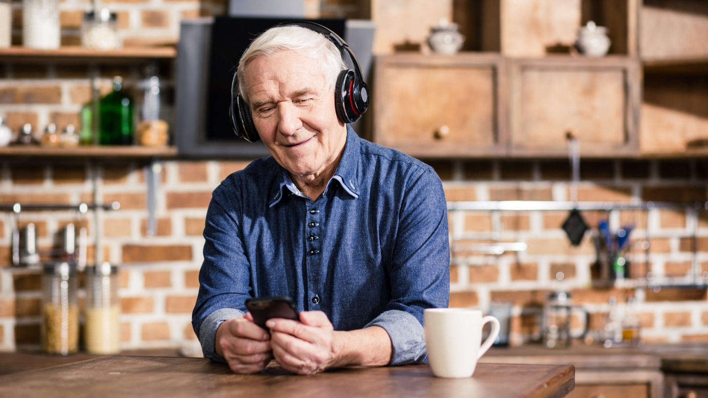 Switch it on. Pleasant smiling elderly man using his smartphone while listening to music
