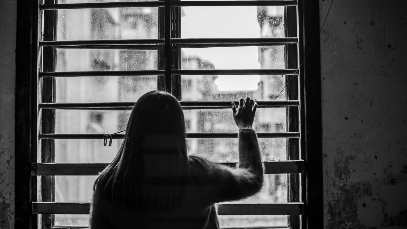 rear-view-sad-woman-window