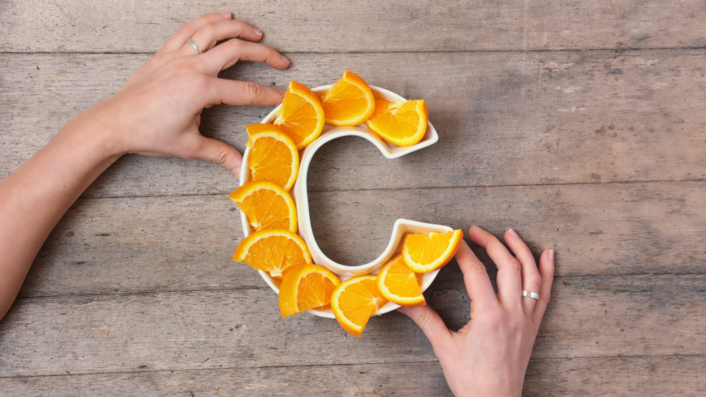 Vitamin C nutrient in food concept. Woman hands holding plate in shape of letter C with orange slices on wooden background. Flat lay or top view. Ascorbic acid is important for immune system function.