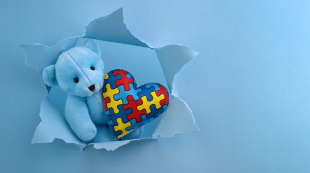 World Autism Awareness, concept with teddy bear holding puzzle or jigsaw pattern on heart in blue paper cut hole