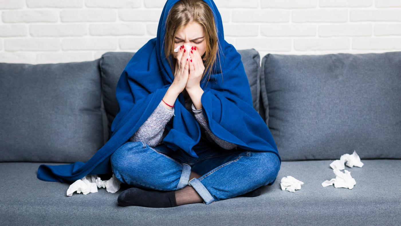 Sick woman with rheum and headache holding napkin, sitting on sofa with coverlet and pills at home